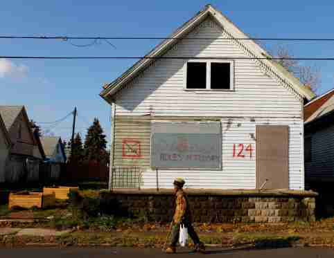 A man walks past an empty house marked for demolition in the Broadway-Fillmore neighborhood of Buffalo, New York, November 20, 2009.  Buffalo has 15,000 vacant lots from houses that have been demolished, amounting to 3200 acres of vacant land.   REUTERS/Brian Snyder    (UNITED STATES BUSINESS SOCIETY)