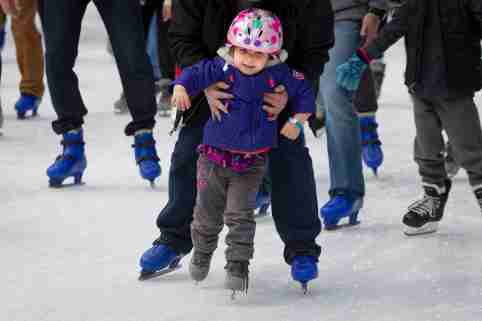 A child gets some help with balance as they skate at the Bryant Park Skating rink in the Manhattan borough of New York November 30, 2014.          REUTERS/Carlo Allegri      (UNITED STATES - Tags: SOCIETY TRAVEL) - GM1EAC10E0T01