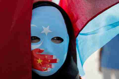An ethnic Uighur demonstrator wears a mask as she attends a protest against China in front of the Chinese Consulate in Istanbul, Turkey, October 1, 2019. REUTERS/Huseyin Aldemir - RC140C0988D0
