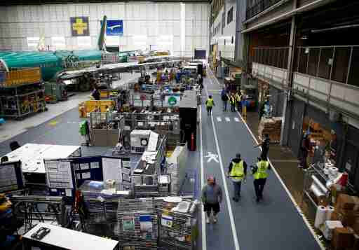 Workers walk by a 737 Max aircraft on the production line at the Boeing factory in Renton, Washington, U.S., March 27, 2019.  REUTERS/Lindsey Wasson