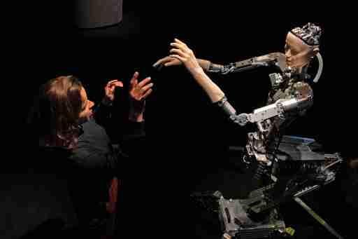 A women interacts with 'Alter', a machine body with a human like face and hands who learns through interplaying with the surrounding world. Alter was created by roboticist Hiroshi Ishiguro and is on display at the 'AI: More Than Human' exhibition at the Barbican Centre in London. The major new exhibition explores the relationship between humans and artificial intelligence.