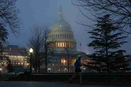 A man runs past the U.S. Capitol dome early in the morning on another day of the continued impeachment inquiry hearings into President Donald Trump's dealings with Ukraine on Capitol Hill in Washington, U.S., December 9, 2019. REUTERS/Loren Elliott