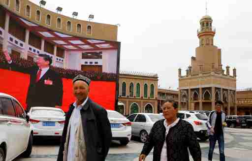 Ethnic Uighur people walk in front of a giant screen with a picture of Chinese President Xi Jinping in the main city square in Kashgar in Xinjiang Uighur Autonomous Region, China September 6, 2018. The screen broadcasts a slideshow of images of Xi on loop, including propaganda images of his previous visit to Xinjiang. Picture taken September 6, 2018. To match Special Report MUSLIMS-CAMPS/CHINA REUTERS/Thomas Peter - RC1DD356DCF0