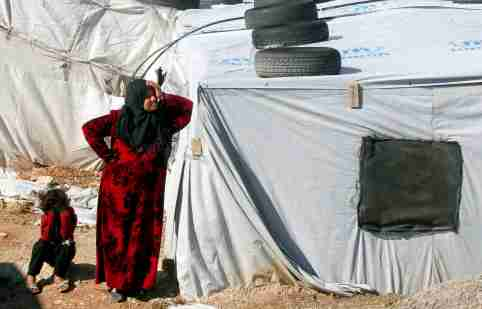 FILE PHOTO: A Syrian refugee woman stands outside a tent at a camp in Bar Elias, in the Bekaa Valley, Lebanon January 13, 2020. Picture taken January 13, 2020. REUTERS/Mohamed Azakir/File Photo