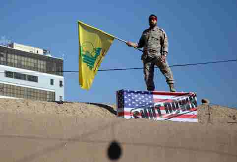 An Iranian guard holds a Hezbollah flag during a funeral procession and burial for Iranian Major-General Qassem Soleimani, head of the elite Quds Force, who was killed in an air strike at Baghdad airport, at his hometown in Kerman, Iran January 7, 2020. Mehdi Bolourian/Fars News Agency/WANA (West Asia News Agency) via REUTERS ATTENTION EDITORS - THIS IMAGE HAS BEEN SUPPLIED BY A THIRD PARTY