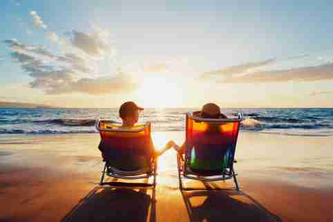 retired couple sits on the beach