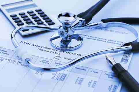 A stethoscope rests atop medical bills