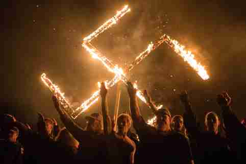 "Supporters of the National Socialist Movement, a white nationalist political group, give Nazi salutes while taking part in a swastika burning at an undisclosed location in Georgia, U.S., April 21, 2018. REUTERS/Go Nakamura    SEARCH ""POY GLOBAL"" FOR FOR THIS STORY. SEARCH ""REUTERS POY"" FOR ALL BEST OF 2018 PACKAGES. TPX IMAGES OF THE DAY."