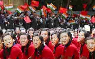 Students wear masks of China's President Xi Jinping as other waves national flags of India and China, ahead of the informal summit with India's Prime Minister Narendra Modi, at a school in Chennai, India, October 10, 2019. REUTERS/P. Ravikumar     TPX IMAGES OF THE DAY