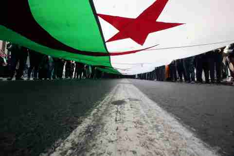 Demonstrators carry a national flag as they march, a year since the start of weekly protests calling for a complete overhaul of the ruling elite, an end to corruption and the army's withdrawal from politics, in Algiers, Algeria, February 14, 2020. REUTERS/Ramzi Boudina