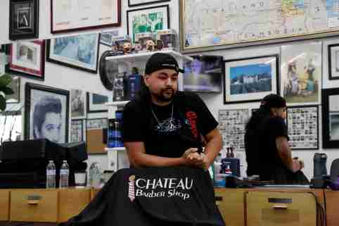 """Barber Adan Covarrubias, 28, stands behind his chair, prior to California's Governor Gavin Newsom's effective immediately statewide """"stay at home order"""", in the face of the fast-spreading pandemic coronavirus (COVID-19), at the Chateau Barber Shop in Napa, California, U.S. March 19, 2020. Picture taken March 19, 2020. REUTERS/Shannon Stapleton"""