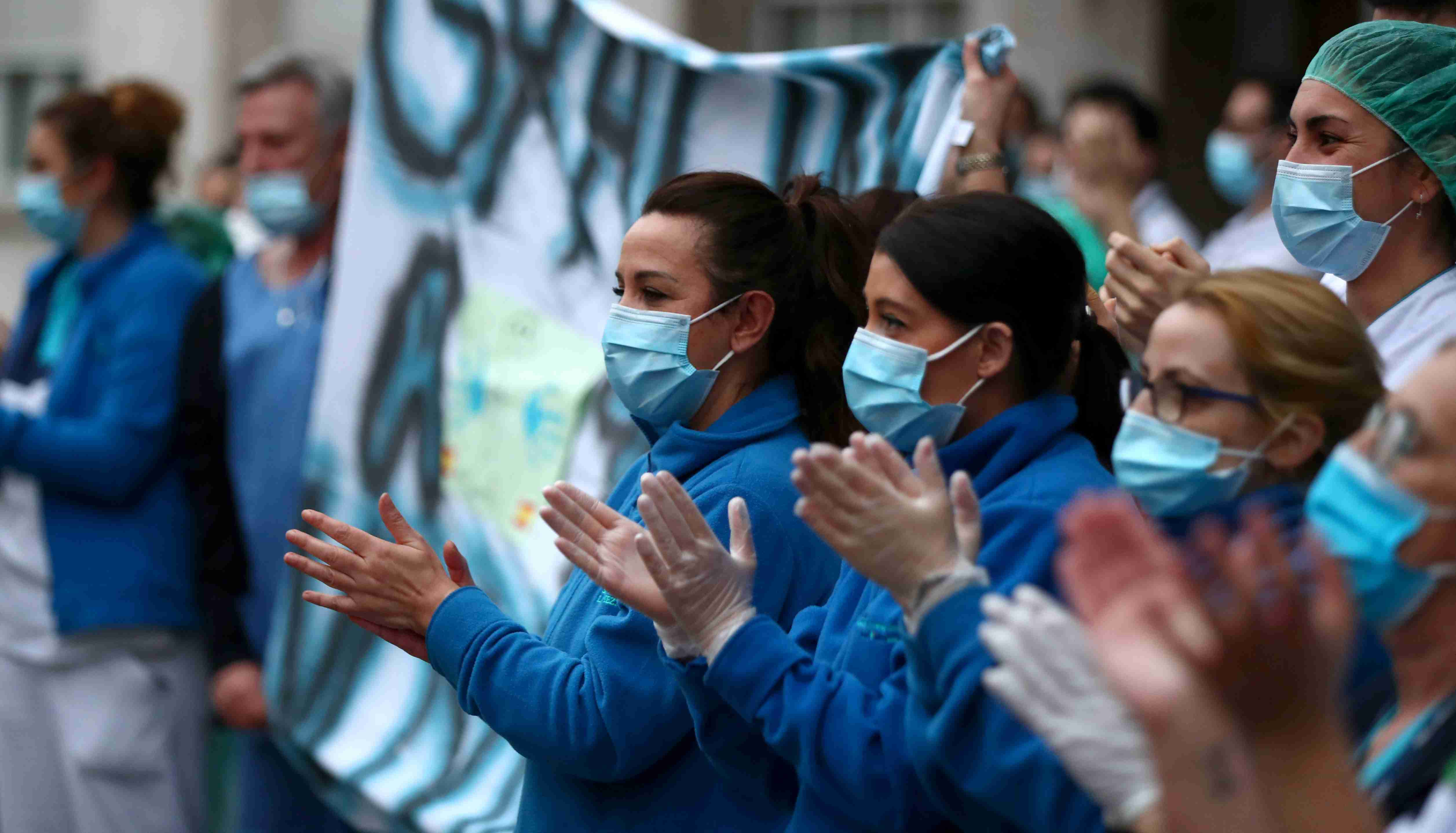 Medical staff from Fundacion Jimenez Diaz hospital react as neighbours applaud from their balconies in support for healthcare workers, amid the coronavirus disease (COVID-19) outbreak, in Madrid, Spain, March 30, 2020. REUTERS/Sergio Perez