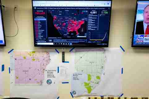 A screen displaying statistics of the spread of coronavirus is hung on the wall above different maps in St. Clair County's emergency operation center Wednesday, April 1, 2020.20200401 Emergency Operation Center Coronavirus 0006