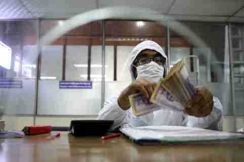 A government bank employee wears a protective suit while counting money amid the coronavirus disease (COVID-19) outbreak in Dhaka, Bangladesh, April 2, 2020. REUTERS/Mohammad Ponir Hossain