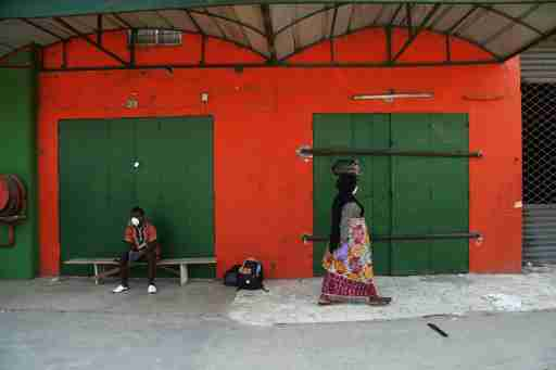 People are pictured in front of closed shops of a market, as the authorities prepare to disinfect the markets amid the outbreak of coronavirus disease (COVID-19) in Abidjan, Ivory Coast March 27, 2020. REUTERS/Luc Gnago