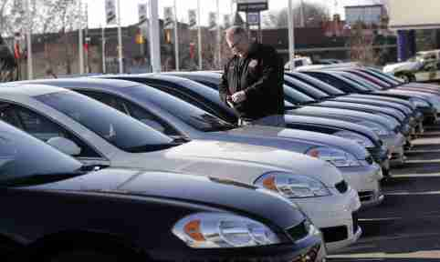A potential customer looks at a 2009 Chevrolet Impala sedan at a car dealership in Dearborn, Michigan December 29, 2008. General Motors and Chrysler are scheduled to each receive $4 billion of loan money today from the U.S. Treasury Department according to the terms of their agreement.  REUTERS/Rebecca Cook (UNITED STATES)