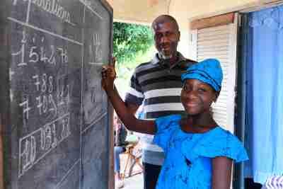 Fatimata Bagayogo, une fillette de 11 ans, étudie à domicile lors de la crise corona, à Odienné, dans le nord de la Côte d'Ivoire. Alors que les écoles sont fermées, elle suit des cours à la télévision et pratique également sur un panneau publicitaire acheté par son père. Sidiki Bagayogo, un homme de 47 ans est enseignant et connaît l'importance de l'éducation.