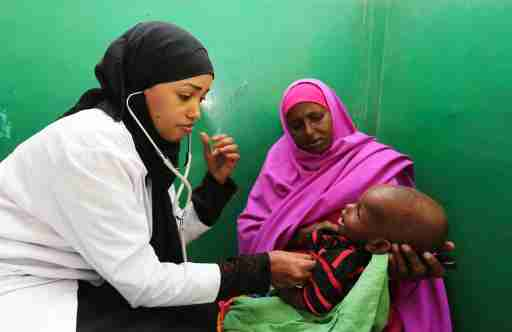 A nurse attends to a child suffering from effects of drinking contaminated water from a well, at a hospital in Yaqshid district in Somalia's capital Mogadishu December 13, 2014. REUTERS/Feisal Omar (SOMALIA - Tags: FOOD HEALTH SOCIETY)