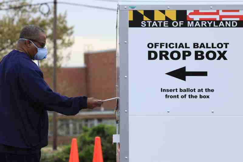 A resident drops off a mail-in ballot at the Edmondson Westside High School Polling site, during the special election for Maryland's 7th congressional district seat, previously held by Rep. Elijah Cummings (D-MD), in Baltimore, Maryland, U.S., April 28, 2020. REUTERS/Tom Brenner