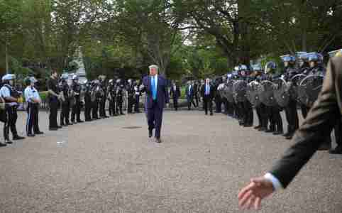 A White House staff member gestures to move the press corps back as U.S. President Donald Trump walks between lines of riot police for a photo opportunity at St John's Church during ongoing protests over racial inequality in the wake of the death of George Floyd while in Minneapolis police custody, near the White House in Washington, U.S., June 1, 2020. REUTERS/Tom Brenner