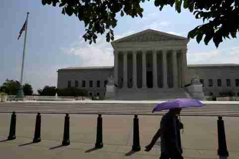FILE PHOTO: A pedestrian holding an umbrella walks along First Street, as a series of rulings are issued at the United States Supreme Court in Washington, U.S., July 6, 2020. REUTERS/Tom Brenner/File Photo