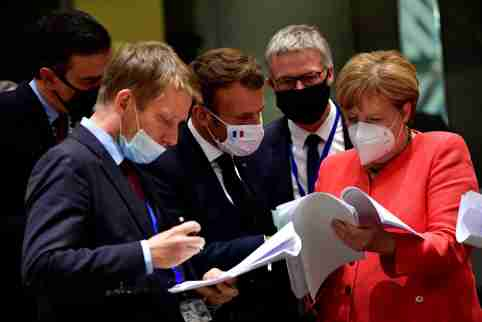 Spain's Prime Minister Pedro Sanchez, France's President Emmanuel Macron and German Chancellor Angela Merkel look into documents during the first face-to-face EU summit since the coronavirus disease (COVID-19) outbreak, in Brussels, Belgium July 20, 2020. John Thys/Pool via REUTERS
