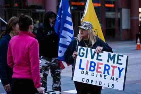 A Donald Trump supporter protests the extension of the stay-at-home order outside the Thompson Center in Chicago on May 1, 2020. The modified stay-at-home order by Illinois Governor J.B. Pritzker runs through the end of May to slow the spread of COVID-19 and now requires people to wear a face covering when entering businesses or when social distancing in public places is not possible. (Photo by Max Herman/Sipa USA)No Use UK. No Use Germany.