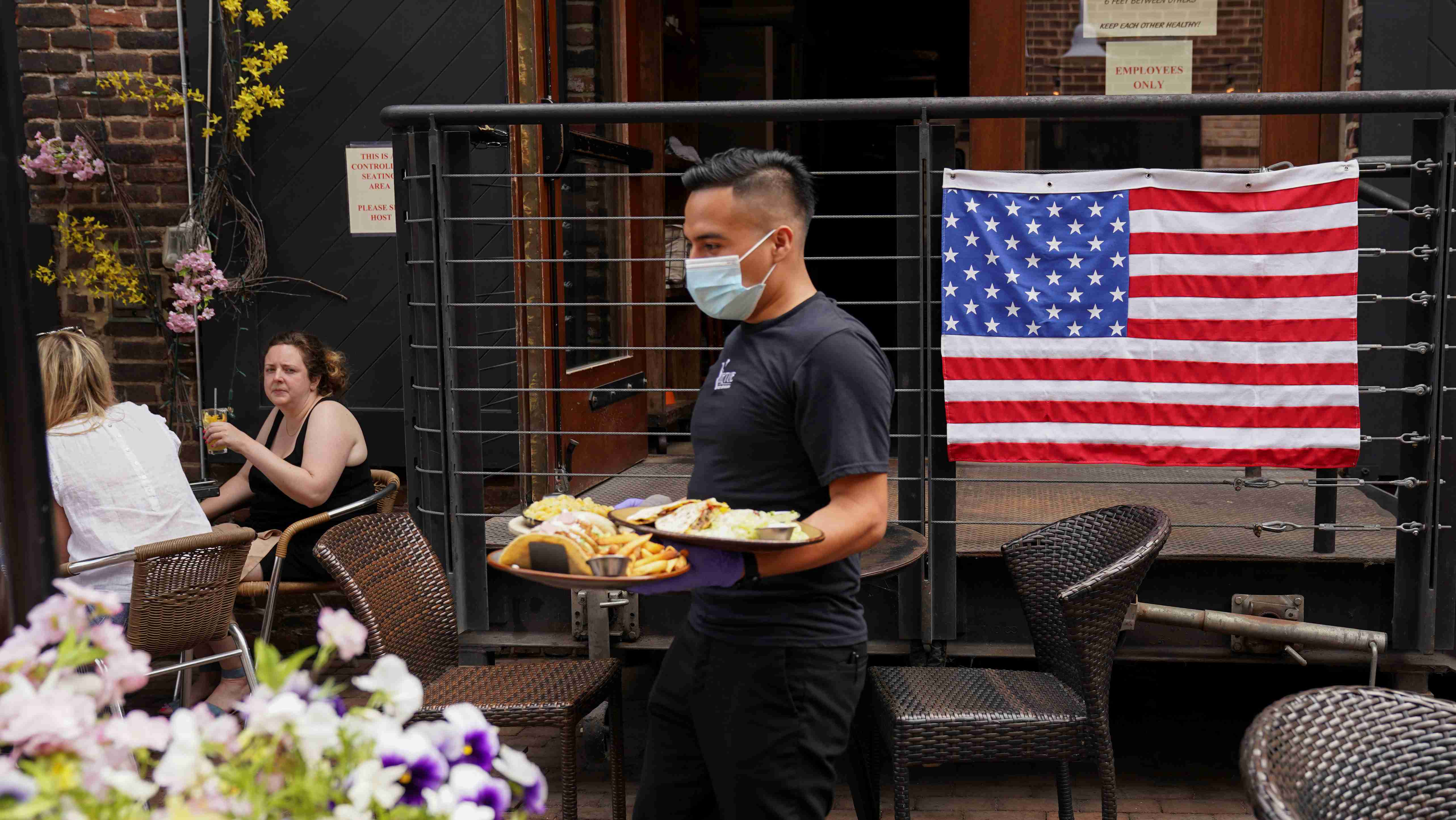 As Phase One of reopening begins in Northern Virginia today, a waiter in a face mask to protect against the coronavirus (COVID-19) serves diners seated outdoors at a restaurant in Alexandria, Virginia, U.S., May 29, 2020.  REUTERS/Kevin Lamarque