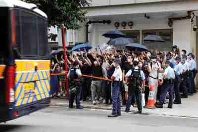 Supporters raise white paper to avoid slogans banned under the national security law as they support arrested anti-law protester, as a prison van leaves Eastern court in Hong Kong, China July 3, 2020. REUTERS/Tyrone Siu