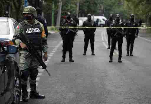 A soldier stands near police officers guarding a crime scene following an assassination attempt of Mexico City's chief of police Omar Garcia Harfuch, at the upscale neighborhood of Lomas de Chapultepec, in Mexico City, Mexico June 26, 2020. REUTERS/Luis Cortes
