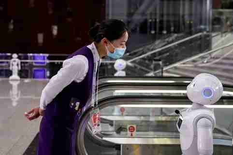 A staff member wearing a face mask following the COVID-19 outbreak looks at a robot at the venue for the World Artificial Intelligence Conference in Shanghai, China on July 9, 2020.