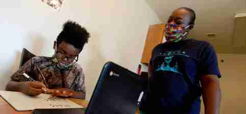 Malik Gordon, a sixth grader at Nashville Classical Charter School, sits with his mother, Victoria, as he does online learning on Thursday, Aug. 20, 2020. Victoria Gordon had to quit her job to support him academically, but they are still experiencing challenges with virtual schooling.Nas Remote Learning Inequities 003 1