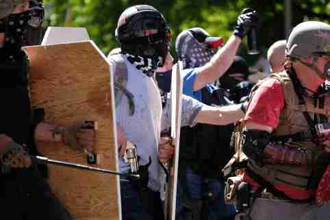 A Trump supporter reaches for his revolver as Black Lives Matter protesters advance to push the group away from the Justice Center in Portland, Ore., on August 22, 2020. (Photo by Alex Milan Tracy/Sipa USA)No Use UK. No Use Germany.