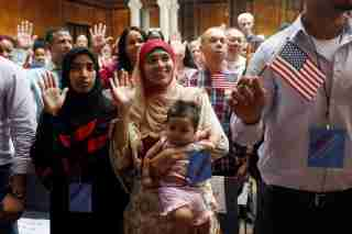 New citizens stand during the Pledge of Allegiance at the U.S. Citizenship and Immigration Services (USCIS) naturalization ceremony at the New York Public Library in Manhattan, New York, U.S., July 3, 2018.  REUTERS/Shannon Stapleton