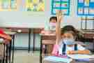 School kids wearing protective mask in classroom and raising hands