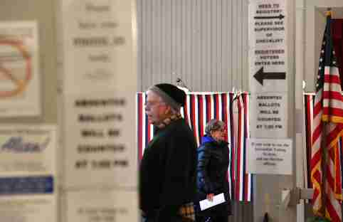 A voter (R) leaves a voting booth after casting her ballot in state's presidential primary election in Greenfield, New Hampshire, U.S. February 11, 2020.    REUTERS/Gretchen Ertl