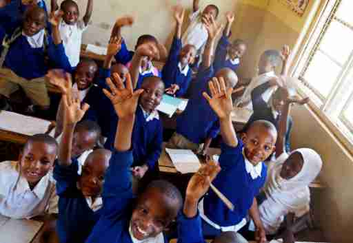 Moshi, Kilimanjaro / Tanzania - 10.06.2015: African children in a class at the Mawenzi Municipal Primary School raise their hands to answer the teacher's question.