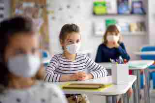 children in classroom wearing masks