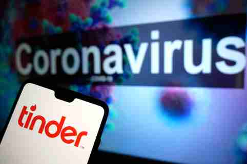 The Tinder dating app logo seen displayed on a mobile phone with an illustrative model of the Coronavirus displayed on a monitor in the background. Photo credit should read: James Warwick/EMPICS Entertainment