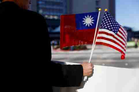 FILE PHOTO: A man holds flags of Taiwan and the United States in support of Taiwanese President Tsai Ing-wen during an stop-over after her visit to Latin America in Burlingame, California, U.S., January 14, 2017. REUTERS/Stephen Lam/File Photo