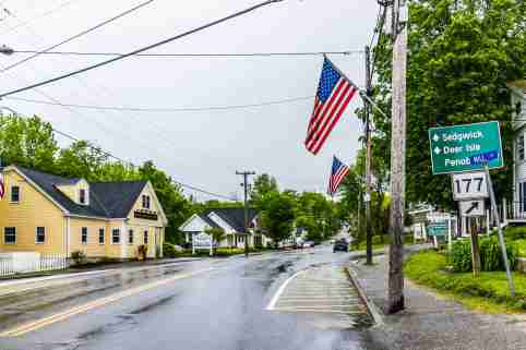Blue Hill, USA - June 9, 2017: American flag on city main street in Maine during rainy cloudy weather with directions