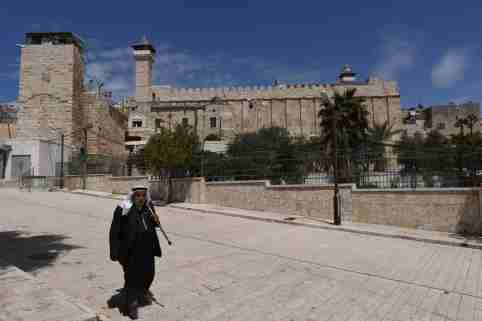 April 6, 2019 - Hebron, Palestine: A Palestinian man walks in front of the Cave of the Patriarchs in the part of the old city controlled by Jewish settlers under the protection of the Israeli militaryScene de la vie quotidienne dans la vieille ville d'Hebron, dont une partie est controlee par des colons juifs sous la protection de l'armee israelienne.NO USE FRANCE