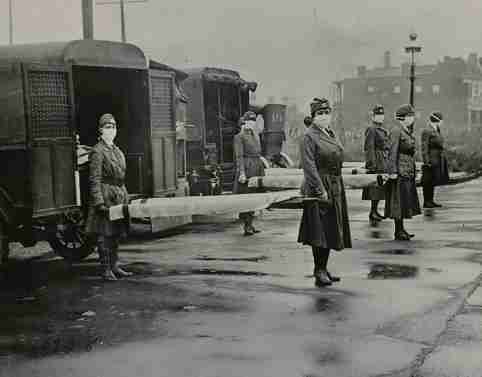 Mask-wearing women hold stretchers near ambulances during the Spanish Flu pandemic in St. Louis, Missouri, in October 1918.