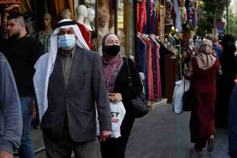 People, some wearing protective masks, walk in downtown Amman, amid fears over rising numbers of the coronavirus disease (COVID-19) cases, Jordan November 4, 2020. REUTERS/Muhammad Hamed