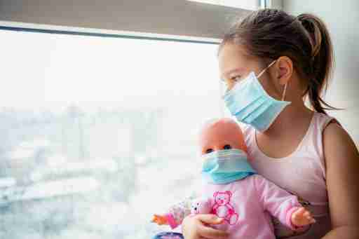 Little girl holding a doll and looking out a window wearing surgical masks.