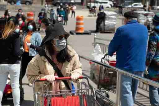 People standing in line for the grocery store with surgical masks on.