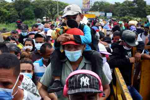 People wearing protective face masks line up to cross the border between Colombia and Venezuela at Simon Bolivar international bridge in Cucuta, Colombia March 12, 2020. REUTERS/Carlos Eduardo Ramirez