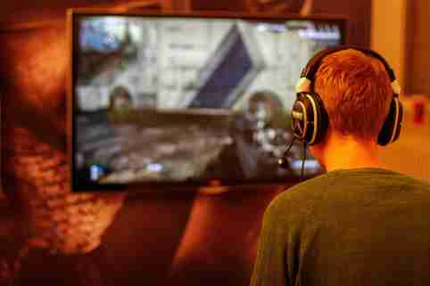 A gamer wearing headphones plays the Call of Duty first person shooter.
