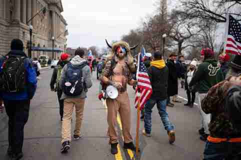"Jake Angeli, a QAnon influencer known as the ""Q Shaman"", is seen among pro-Trump supporters during protests in Washington, D.C., on Jan. 6, 2021"