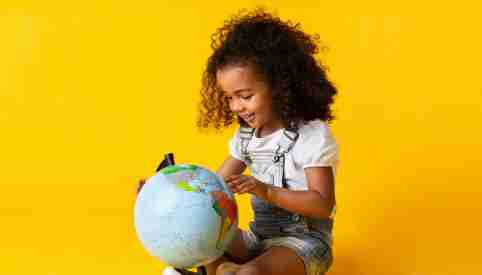 A girl looks at a globe.